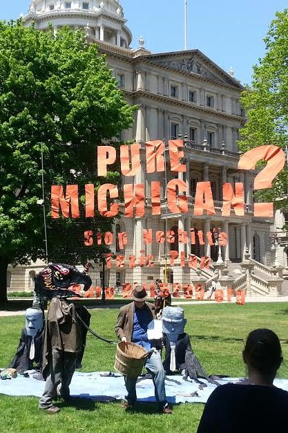 "Theatre Demonstration in front of sign reading ""Pure Michigan? Stop Nesbitt's Toxic Plan"""